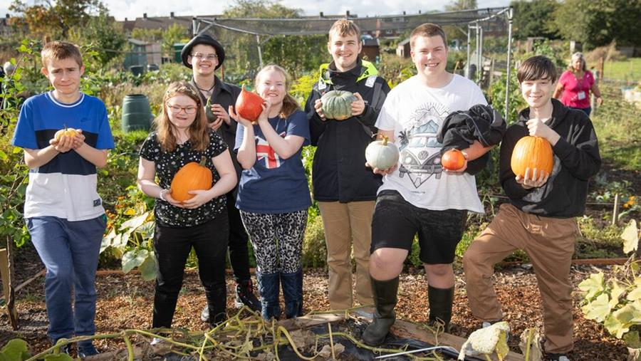 Students hold harvested squash and pumpkins in an allotment.