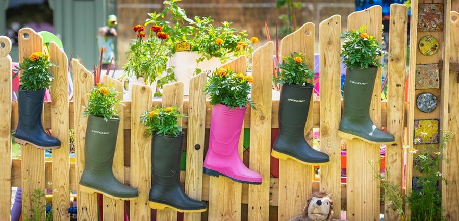 Wellies planted with marigolds hang from a wooden fence.