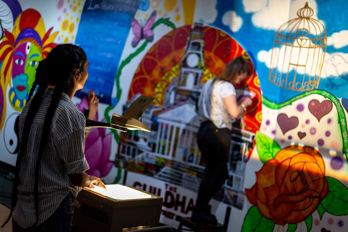 Scene from a wall mural workshop with young people. Artist stood behind an over head projector helping mural design element stay in place for a young person drawing around the shadow created on wall