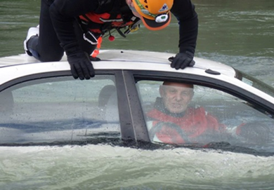 A rescuer is on the roof of a car submerged in water, while the driver looks out the driver's window.