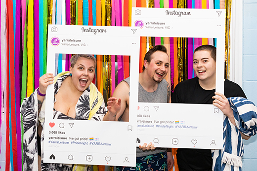 People having fun at the Pride Night photo wall with the Yarra Leisure Instagram frames