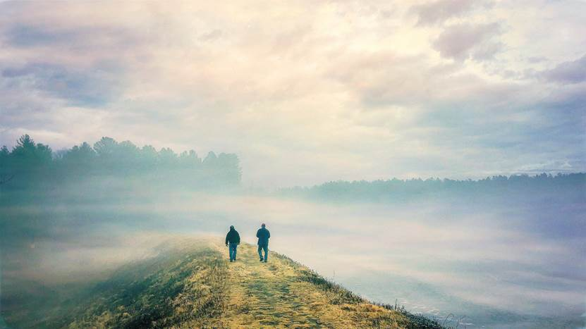 Two men walking away from the camera on a foggy causeway
