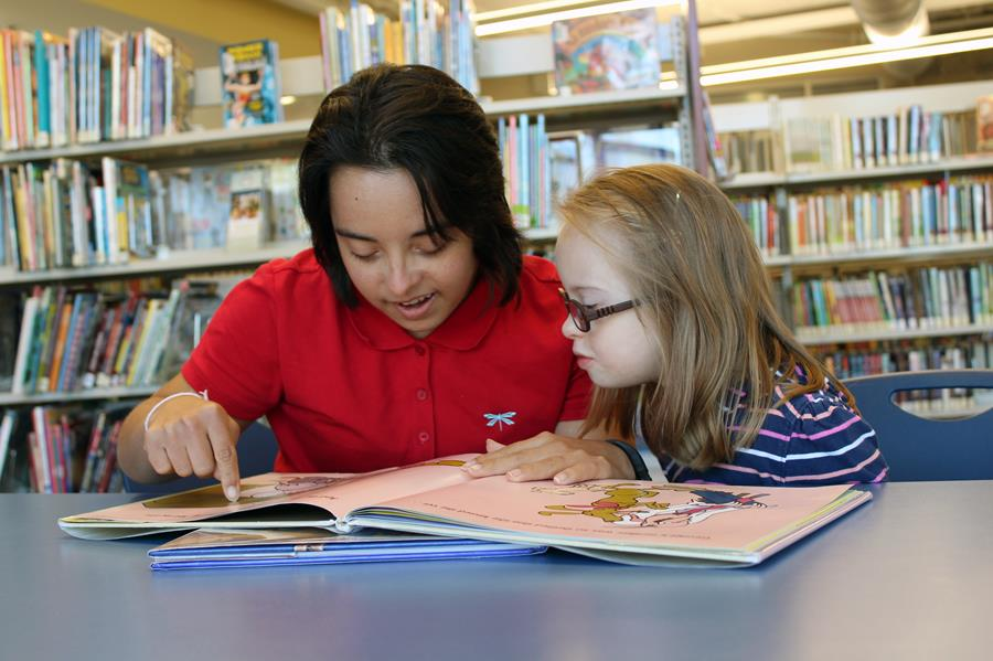 Young woman with Down syndrome teaching a child with Down syndrome to read.