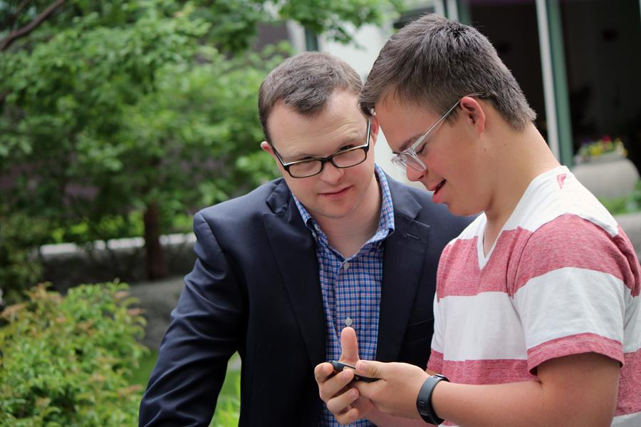 Two young men with Down syndrome working on a phone.