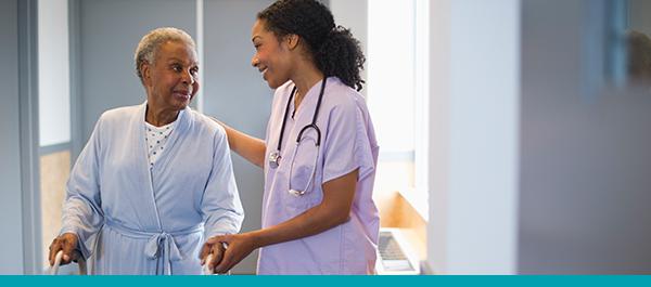 Photo of nurse assisting elderly female patient