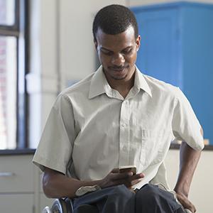 Homme assis en fauteuil roulant, vérifiant son smartphone
