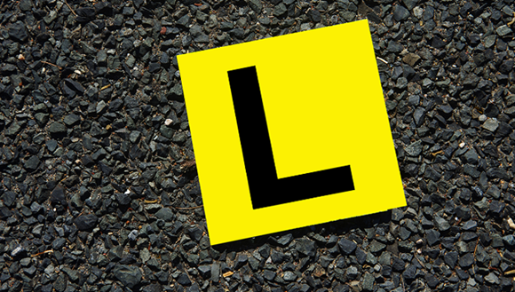 Yellow Learners plate on road
