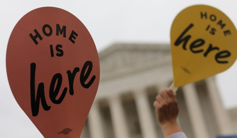 "Two ""Home is Here"" signs in front of the Supreme Court of the United States"