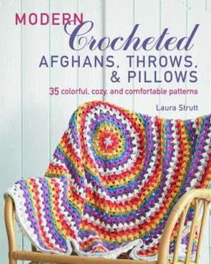 This is the cover image for Modern Crocheted afghans, throws and pillows. 35 colorful cozy and comfortable patterns. The cover image is of a colorful crocheted throw which is draped over a rattan chair.