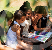 Children sit on grass and read a book together. Image from the cover of the NCCDH's 2013 report, guide to community engagement frameworks for action on the social determinants of health and health equity.