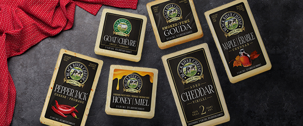 Six Black River Cheese packaged products: Pepper Jack Cheese, Goat Cheese, Cheddar with Honey, Smoked Gouda, 2 Year Aged Cheddar, and Maple Cheddar.