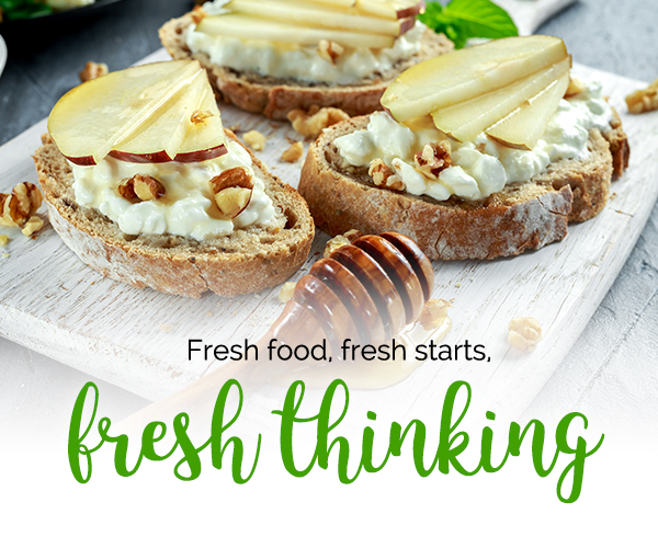 Photo of  whole grain baguette slices topped with cottage cheese, pear slices, chopped walnuts, and drizzled with honey.