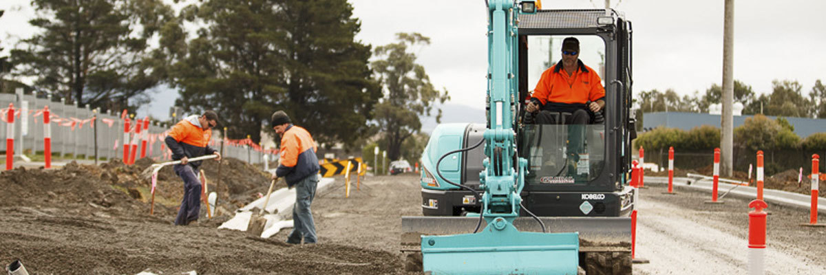 People constructing a road with machinery and safety equipment