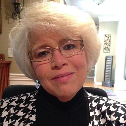 Smiling woman with white hair and glasses.
