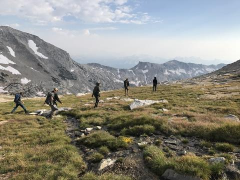 Five hikers traverse a high alpine meadow with short grass and a few rocks. Behind them are bare rock mountains with a few snow patches. Photo by Kylie Chappell.
