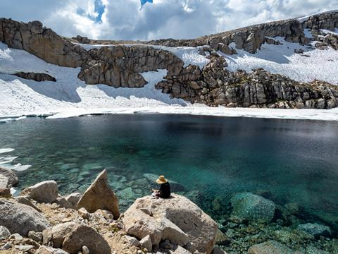 An artist wearing a wide-brimmed hat paints overlooking a clear alpine lake.