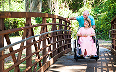 Man pushing woman in wheelchair along walkway