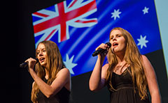 Two girls singing in front of Australian flag