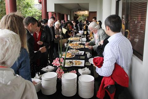 Attendees trying the food at the buffet.