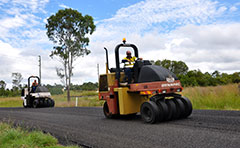 A photo of a roller compressing road works in the region.