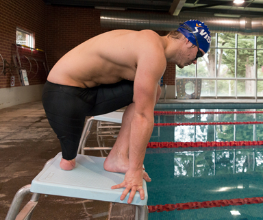 Man who is an amputee, in position on the starting block at a swimming pool