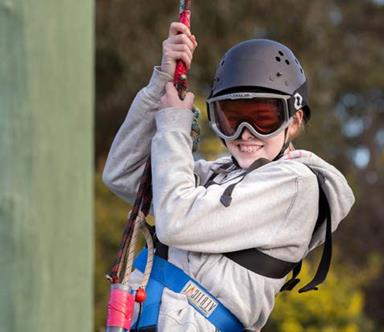 Girl wearing a sports helmet and harness.