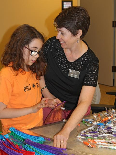 Community Engagement Officer Carly Brown and helper assemble dental kits.