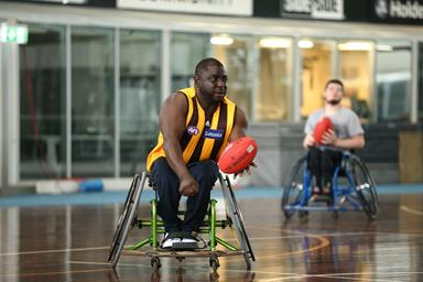 Man in a wheelchair holding a football