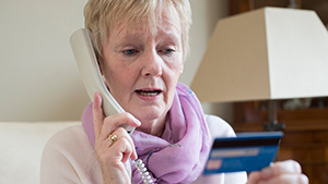Mature woman on the phone looking at her credit card