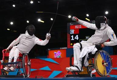 Two people in wheelchairs practicing fencing