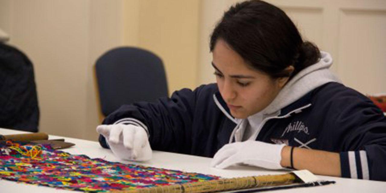 Image of student examining a Guatemalan textile