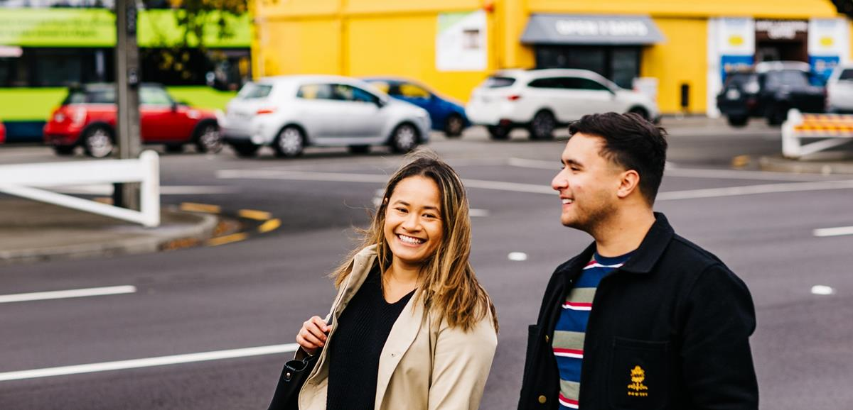 man and women smiling while walking along street
