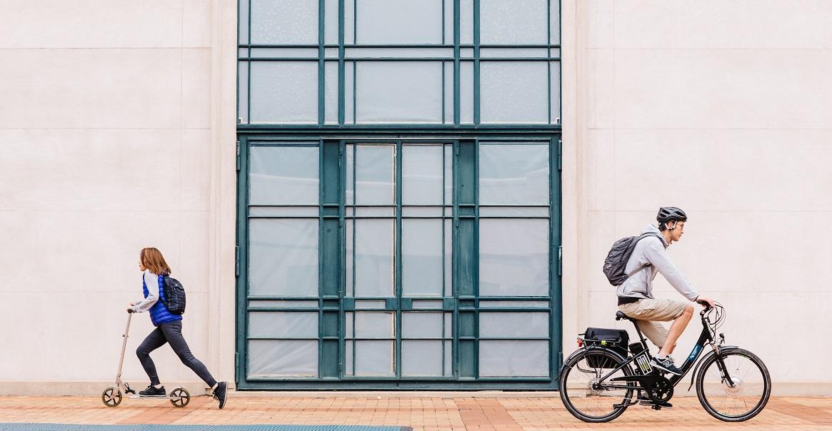 women on scooter, man on bike