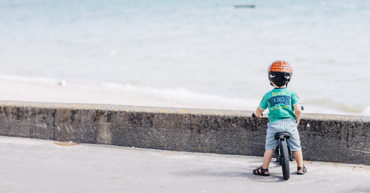 Child on bike looking at beach