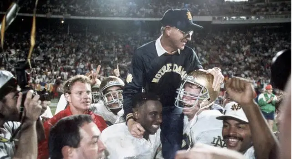 Former Notre Dame football coach, Lou Holtz being lifted up by players