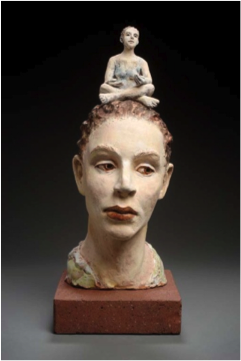 Sculpture of woman's head, with another smaller sculpture of a woman.