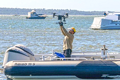 A fisheries officer releasing a drone from a boat