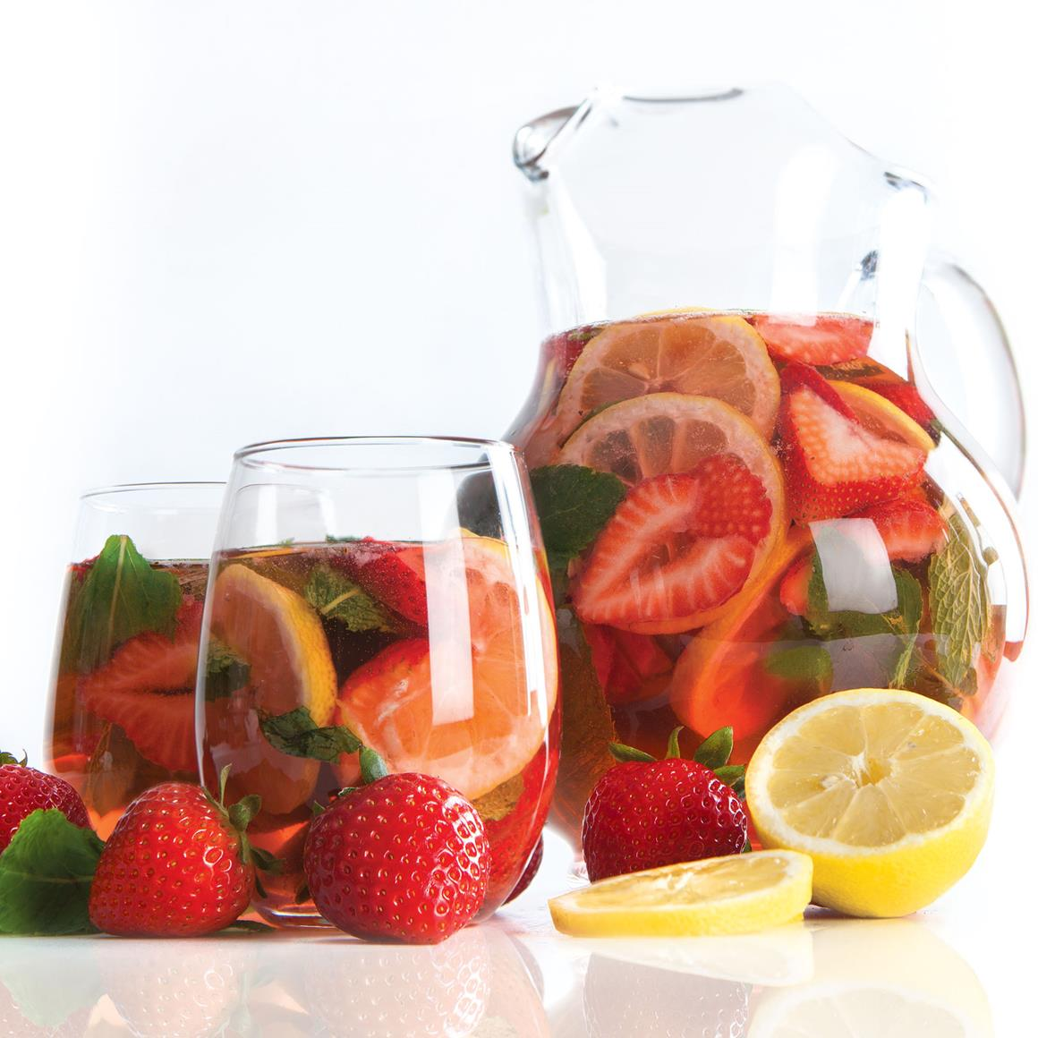 Rosé sangria in glasses and a pitcher with lemon and strawberries