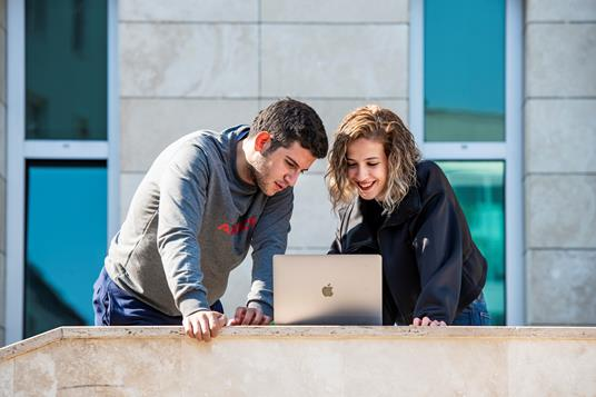 Two young adults interacting with a laptop