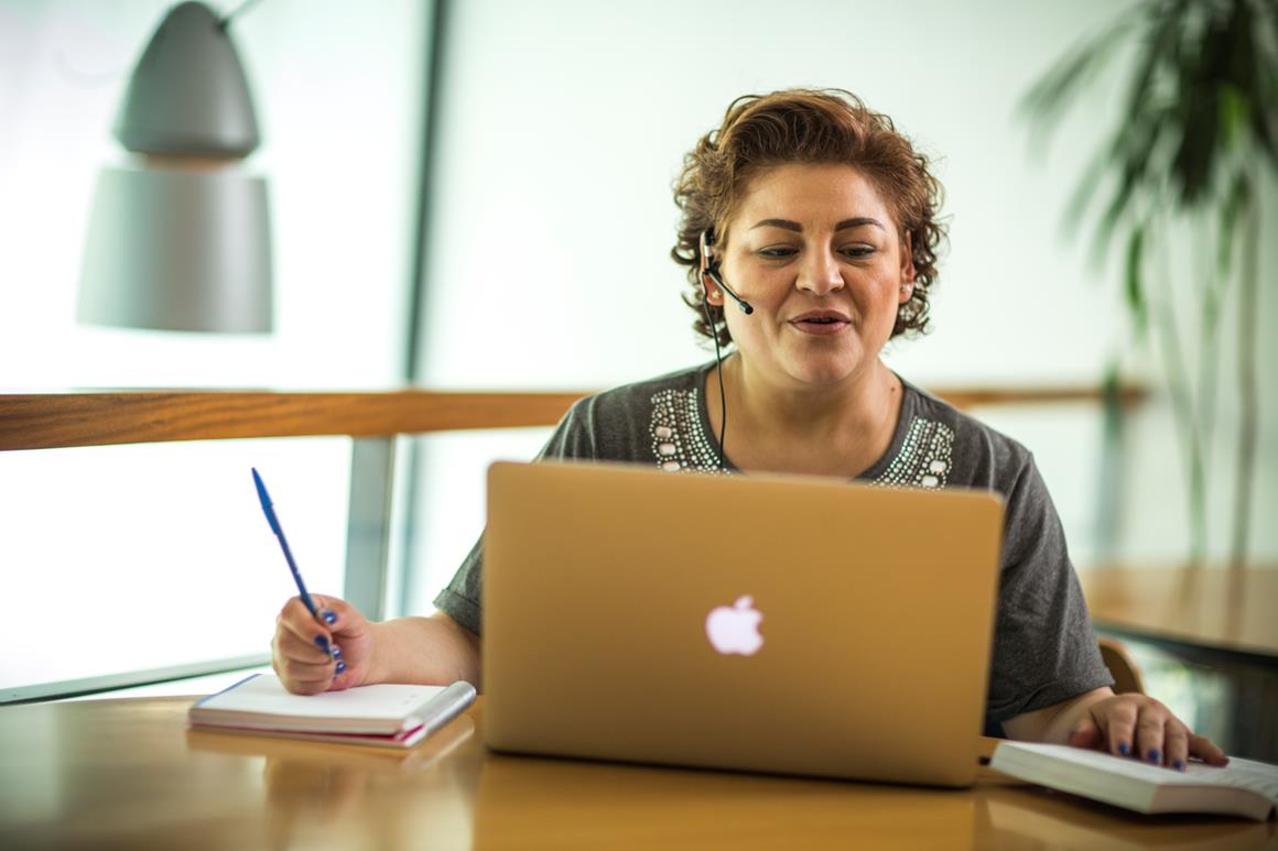 An adult woman sitting on a desk in front of her laptop, with a pen and a pad on her right hand side and an open book on her left. She is wearing headphones with a microphone and seems to be talking.
