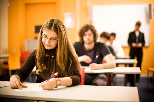 A woman in a classroom taking an exam