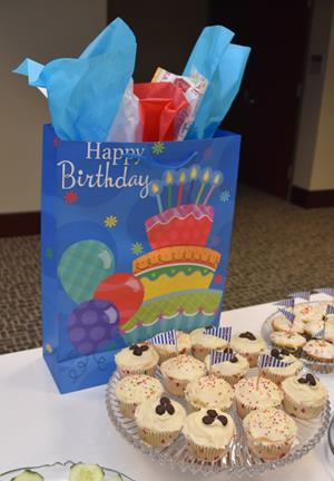 BIrthday display of a gift bag and cupcakes