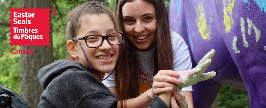 Image of a happy camper with a camp counsellor doing handprint art