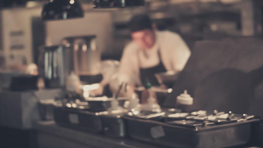 blurred image of a chef working on the line at a restaurant