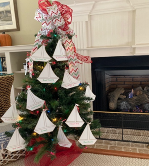 Christmas tree decorated with gift cards and paper ships