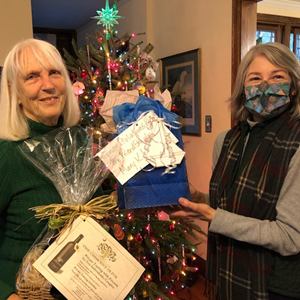 Board member giving second raffle winner her bag of gift cards