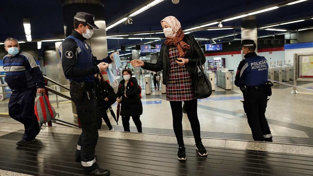 A municipal police officer gives out free protective face masks at a metro station during the lockdown amid the coronavirus disease (COVID-19) outbreak in Madrid, Spain, April 13, 2020.