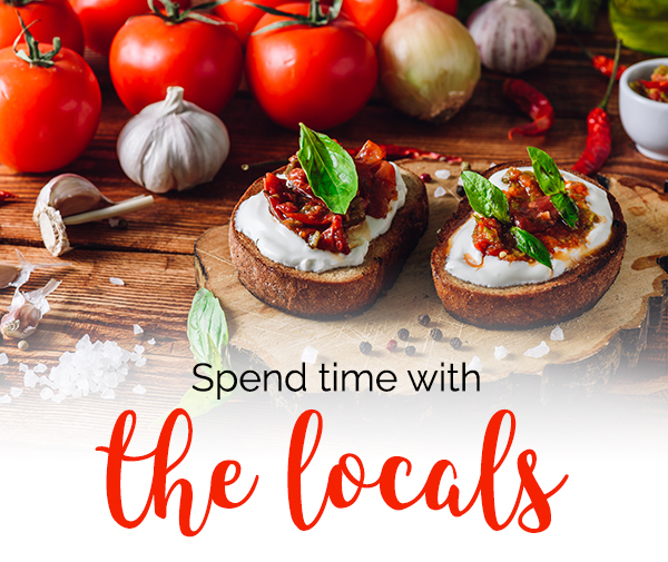 Photo of fresh tomatoes, garlic cloves, and homemade toasted bruschetta on a wooden table + Headline: Spend time with the locals