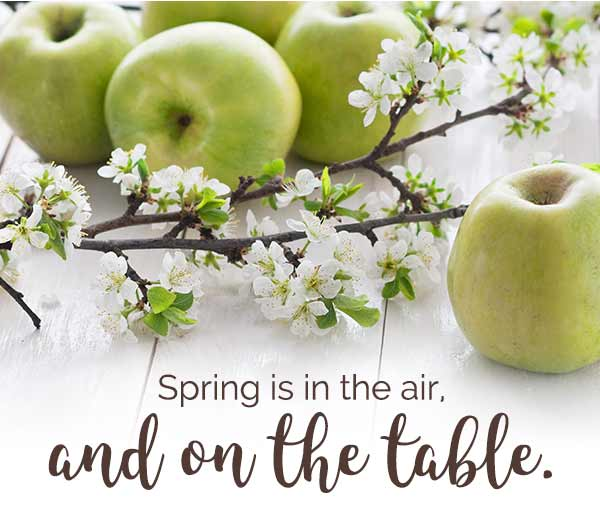 Photo of green apples and apple blossoms on wooden table + Headline: Spring is in the air, and on the table