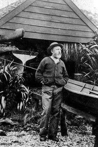 """""""On the watch"""" Richard Henry standing beside the boat shed on Pigeon Island. c.1900"""